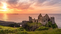 Ruined medieval Dunluce Castle on the cliff at amazing sunset, Wild Atlantic Way, Bushmills, County Antrim, Northern Ireland. Filming location of popular TV show, Game of Thrones, Castle Greyjoy