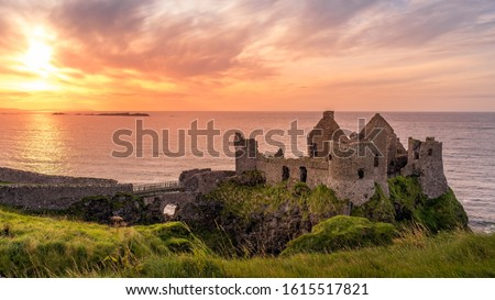 Photo of  Ruined medieval Dunluce Castle on the cliff at amazing sunset, Wild Atlantic Way, Bushmills, County Antrim, Northern Ireland. Filming location of popular TV show, Game of Thrones, Castle Greyjoy