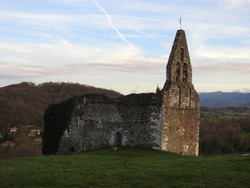 Ruined medieval (14th century) chapel perched on green hill overlooking a panoramic view of the French Pyrenees with hills, soft blue sky and clouds at dusk. Salies-du-Salat, Haute-Garonne, Occitanie