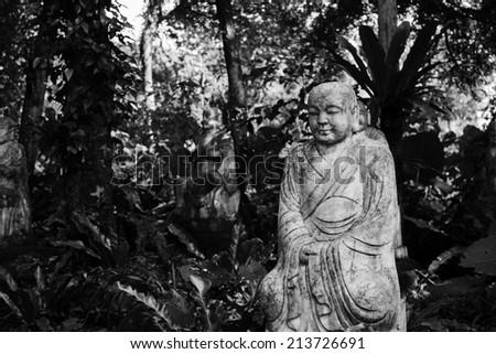 Ruined stone statue Ksitigarbha Bodhisattva in garden.