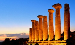 Ruined Temple of Heracles columns in famous ancient Valley of Temples on blue hour sunset in summer evening, Agrigento, Sicily, Italy. UNESCO World Heritage Site.