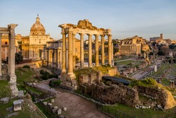 Ruins and columns of Roman Forum in warm light of sunset in Rome, Italy. Popular touristic destination and site. Ruins of Temple of Saturn and basilica.
