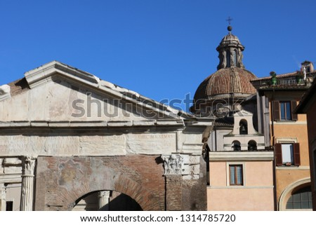 Ruins in Rome next to buildings with Dome in background #1314785720