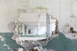 Ruins of a huge empty building seem from a hole in the wall