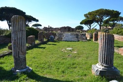 ruins of a temple in ostia antica rome italy with colums and marble stairs with grass and ancient trees blue sky