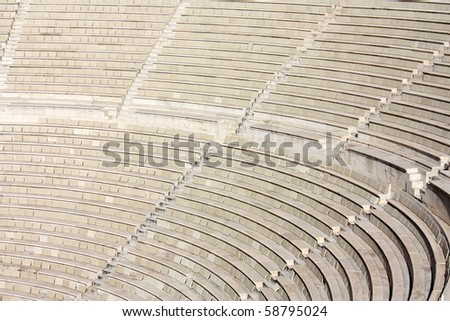Ruins of an ancient greek Amphitheater in Athens, rows of seats and steppes