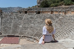 Ruins of an ancient Roman or Greek theater in the city of Demre. The ancient city of the World. Antalya Province, Turkey. Girl sitting back