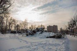 ruins of an old abandoned building in winter, cold weather, a lot of snow fell during day, collapsed walls, roof of demolished residential building in village, on outskirts of city, abandoned people