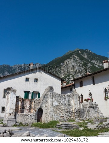 Ruins of ancient buildings preserved in memory of  shattering earthquake of 1976 in Venzone. Blue sky and mountain on background. Friuli, Italy