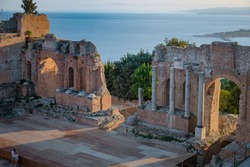 Ruins of Ancient Greek theatre in Taormina on background of Etna Volcano, Italy. Taormina located in Metropolitan City of Messina, on east coast of island of Sicily Europe