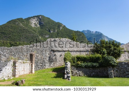 Ruins of ancient stone wall surrounded by nature; preserved in memory of  shattering earthquake of 1976 in Venzone. Friuli, Italy