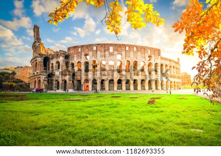 ruins of antique Colosseum with grass lawn in sunise lights, Rome Italy at fall #1182693355