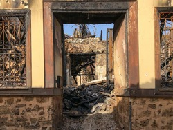 Ruins of burned ancient historical 2 floors house after fire disaster accident in old town of Antalya Kaleici Turkey. Stock image of heaps of ash and arson, collapsed roof and broken windows.
