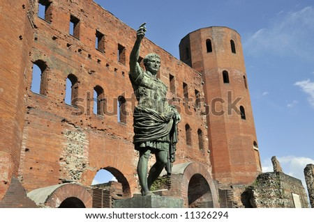 Ruins of gates of roman times with statue on front of it in Turin, Italy - porta palatina