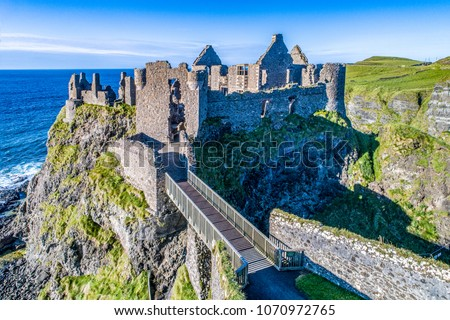 Ruins of medieval Dunluce Castle on a steep cliff. Northern coast of County Antrim, Northern Ireland, UK. Aerial view at sunset light.