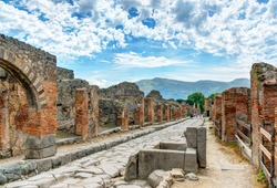 Ruins of Pompeii near Naples, Italy. Pompeii is an ancient Roman city died from the eruption of Mount Vesuvius in 1st century and is a tourist attraction now. Panorama of abandoned street in Pompei.