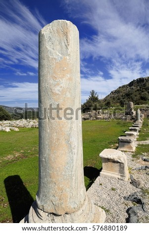Ruins of the agora. Standing column at its S.E.corner and the Inscribed Obelisk on background -inscribed monolith in Ancient Greek-Lycian-Mylian languages dated 425-400 BC.- of Xanthos-Lycia-Turkey. #576880189