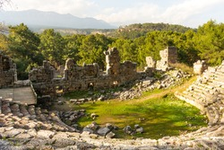 Ruins of the amphitheatre of the ancient ancient city of Phaselis illuminated by the bright sun in sunny weather on mountains and clouds background in Turkey, Antalya, Kemer. Turkey national landmarks