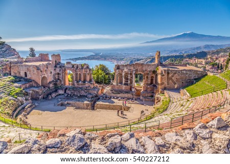 Ruins of the Ancient Greek Theater in Taormina, Sicily with the double smoke tail of the Etna extending over the the Giardini-Naxos bay of the Ionian Sea in the morning sun shine.