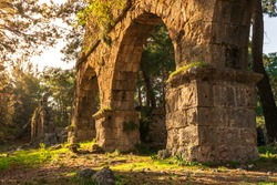Ruins of the aqueduct of the ancient ancient city of Phaselis illuminated by the bright sun in sunny weather in Turkey, Antalya, Kemer. Turkey national nature landmarks. Gates to ancient city