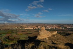 Ruins of the Arab castle in Maria de Huerva near Zaragoza early in the morning with the town and windmills of La Muela in the background