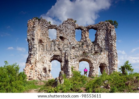 ruins of the castle of Torna in Slovakia with green plants, lovely blue sky and a man under the walls