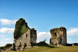 Ruins of the ivy clad Gleaston Castle, a 14th century fortification situated near Ulverston, Cumbria, set against a glorious blue sky with cumulus clouds