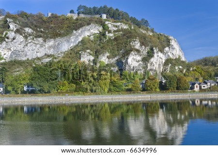 Ruins on a rock by the Maas river. The rock, autumn-looking trees and sky reflecting in the water. Belgium.
