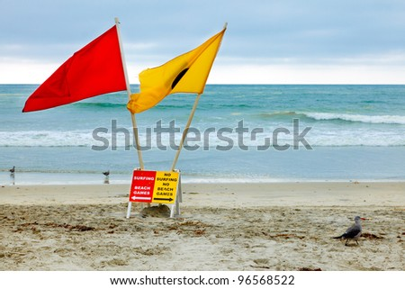 Rules about surfing and beach games at a California Beach - colorful signs and flags