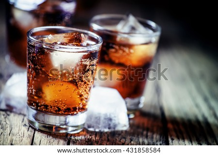 Rum and cola and ice, dark wood background, selective focus, shallow depth of field