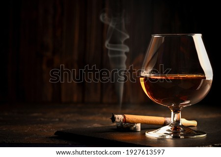 Rum in glasses with a bottle of rum and a cigar in the background. Black background ストックフォト ©