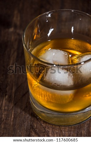 Rum on the rocks on wooden background - stock photo