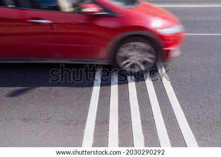 Rumble strips or speed breakers  on asphalt road surface and red car crossing them in motion blur. Traffic calming concept.  Photo stock ©