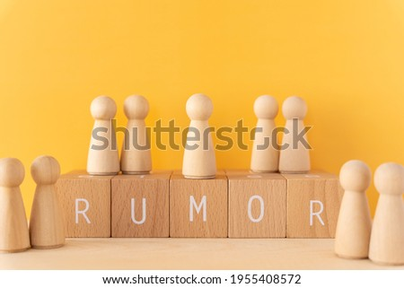 Rumor; Five wooden blocks with 'RUMOR' text of concept and nine human toys. Photo stock ©