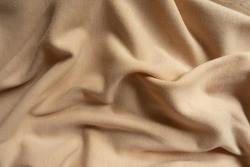 Rumpled simple beige cotton jersey fabric from above