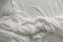 Rumpled white bed sheet and blanket on bed in the morning.