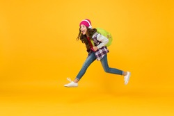Run and jump. Kid captured in mid air. School happiness and joy. Finally vacation. Little girl listen music in headphones. Small schoolgirl running to school. Hurry up. Towards school knowledge.
