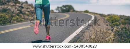 Run athlete woman running on road race training cardio endurance exercising outdoors banner panorama. Crop of lower body legs female person.