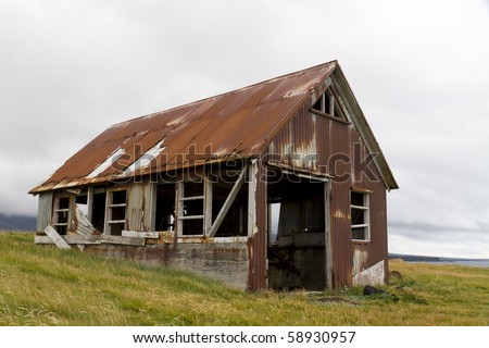 Run down old shed clad in rusty corrugated iron, situated on the coast