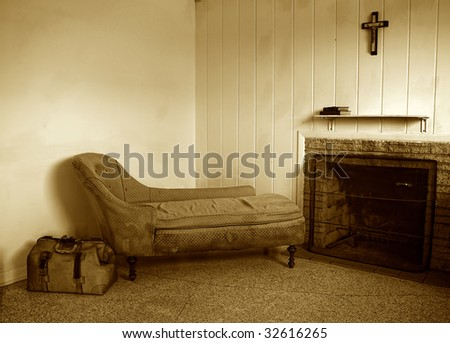 run down room with old sofa and travel bag. There is also a fireplace and a crucifix hanging above the shelf which has two books on it.