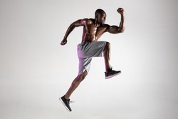 Run for adventures. Young african-american bodybuilder training over grey studio background. Muscular single male model jumping in sportwear. Concept of sport, bodybuilding, healthy lifestyle.