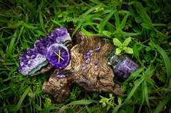 Runestone Gebo (Gift) made from natural amethyst, it iles on the cut of some tree in the green grass. The runic symbol is carved into a polished piece of semi-precious stone.