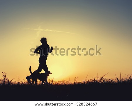 Runner and dog silhouettes in sunset time