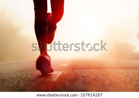 Runner athlete feet running on road. woman fitness silhouette sunrise jog workout wellness concept. - stock photo