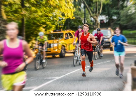 Runner athlete man running in run marathon race in Central Park New York city. People crowd jogging in street urban active lifestyle. Motion blur focus on one person.