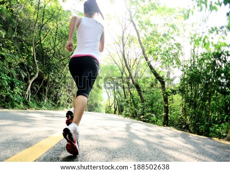 Runner athlete running at forest road. woman fitness jogging workout wellness concept.