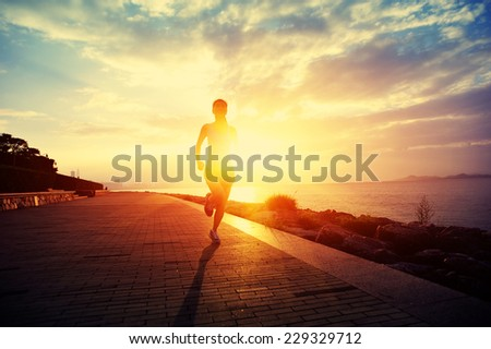 Runner athlete running at seaside. woman fitness silhouette sunrise jogging workout wellness concept.  #229329712