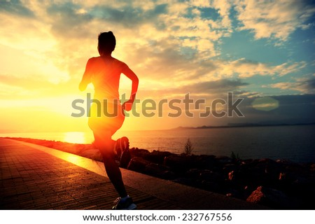 Runner athlete running at seaside. woman fitness silhouette sunrise jogging workout wellness concept.  #232767556