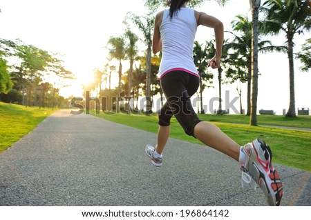 runner athlete running at tropical park woman fitness sunrise jogging workout wellness concept