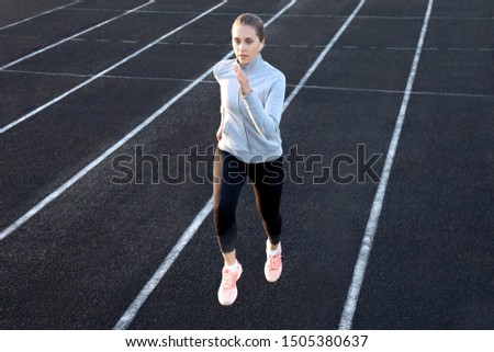 Runner athlete running on athletic track training her cardio in stadium. Jogging at fast pace for competition
